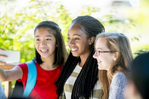 A multi-ethnic group of teenage girls are smiling and taking a selfie together on their cell phones.